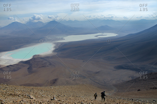 Hikers sliding down mountain towards beautiful lake