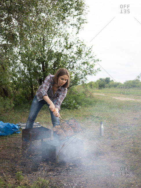Young woman grilling chicken on a charcoal during summer day in forest