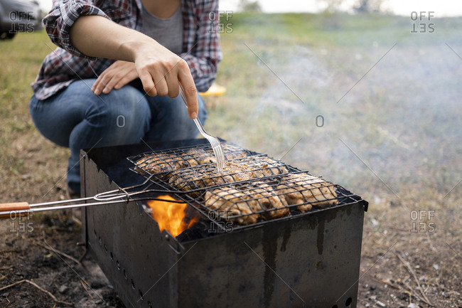 Woman grilling chicken on a charcoal during summer day outdoors