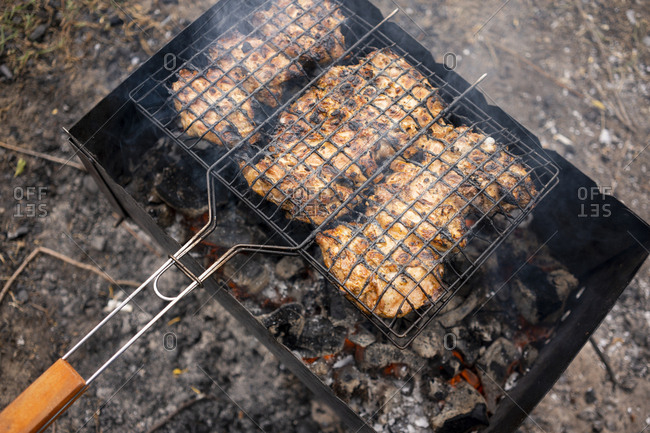 Chicken on hot charcoal grill from overhead outdoors