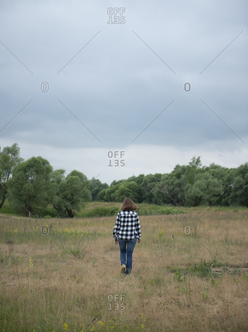 Rear view of woman walking in field against lush trees and moody sky