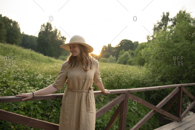 Happy carefree woman in hat standing against green field during sunset