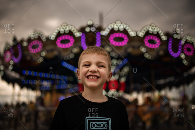 Boy excited at the carnival standing in front of the merry-go-round