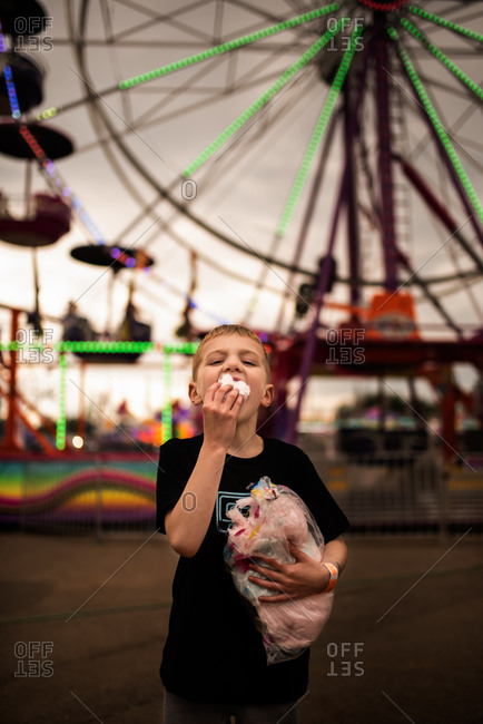 Boy eating cotton candy in front of the ferris wheel at the carnival