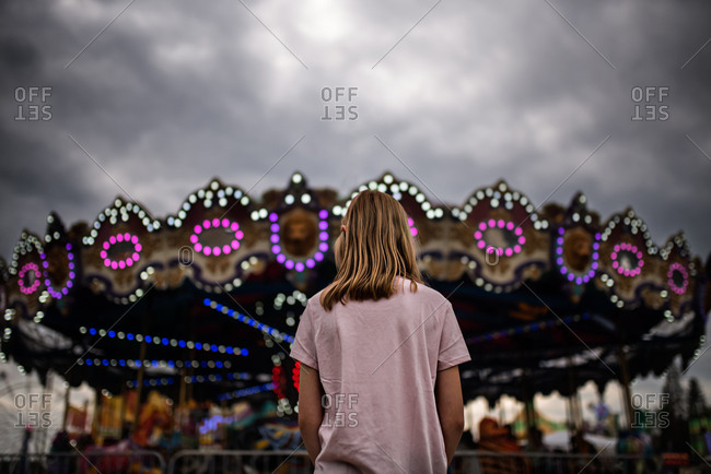 Girl looking at the merry-go-round at the carnival