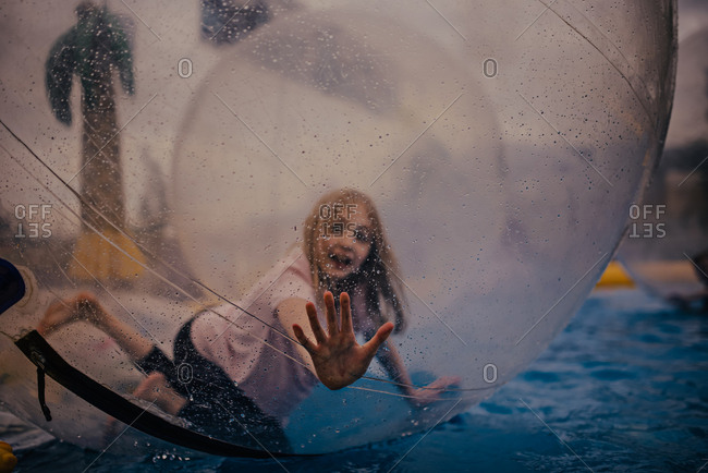 Girl playing in the giant bubble at the carnival