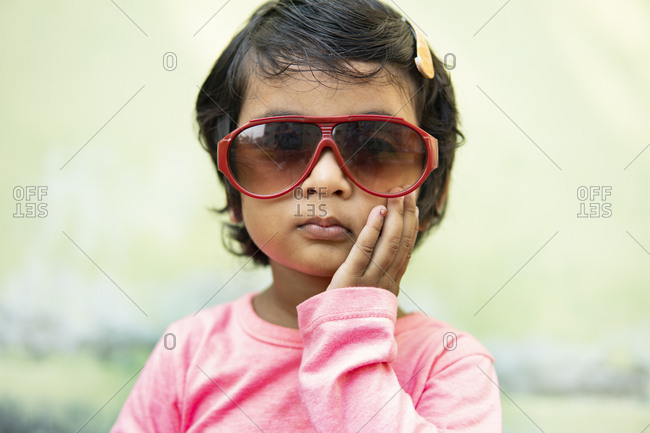 Cute little girl wearing fashionable sunglasses and making fun