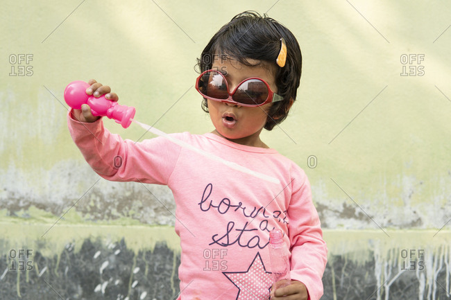 Cute little girl making fun with soap bubbles