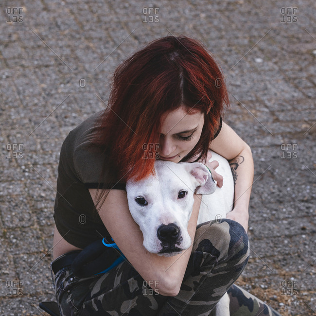 The woman is hugging her dog - dogo argentino