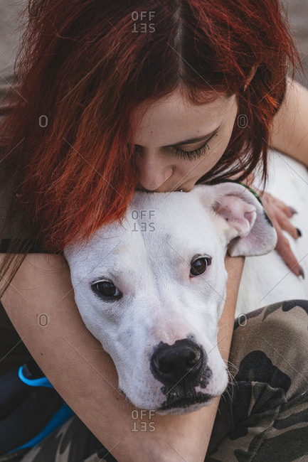 The woman kissing and hugging her large puppy