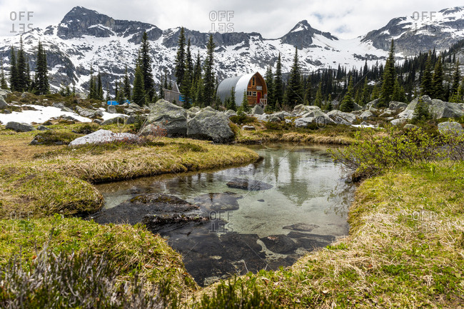 Scenic view of alpine cabin in grassy mountain meadow in canada.