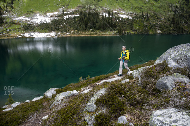Full length view of women hiking by an alpine mountain lake in canada.