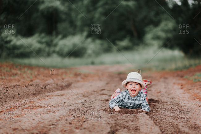 Carefree happy child lying on the ground playing in the dirt smiling