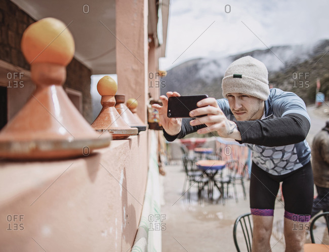 A cyclist with a hat takes a cell phone picture of a moroccan tagine