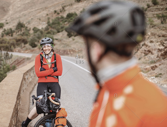 A smiling white female takes a break from biking through morocco