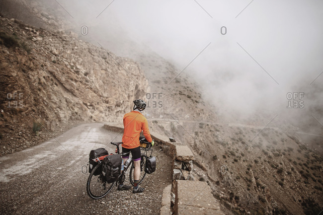 A make cyclist looks at the cloudy view from tizi n test pass, morocco