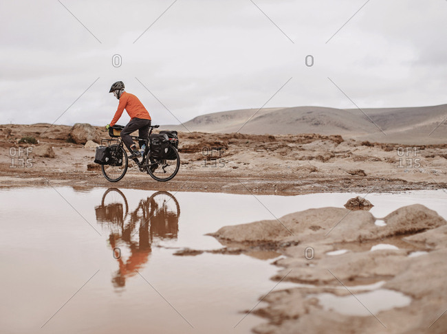 A bike packer is reflected in water on a cold day, taliouine, morocco