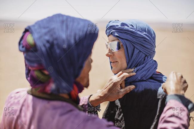 A berber tribesman ties a hijab on a caucasian female tourist, morocco