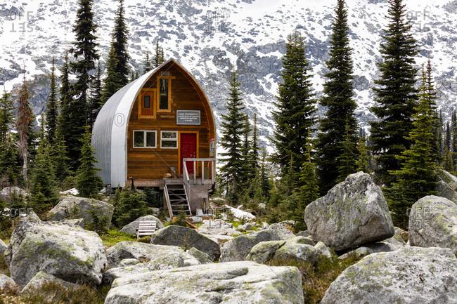Canada, British Columbia, Pemberton - June 21, 2019: Scenic view of alpine cabin in grassy mountain meadow in canada.
