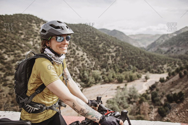 Atlas Mountains, Morocco - April 2, 2019: Female cyclist smiles while biking through the atlas mountains, morocco