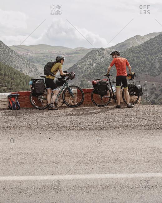 Morocco, Marrakesh-Safi, Asni - April 2, 2019: A couple of bike packers take a break while cycling through morocco.