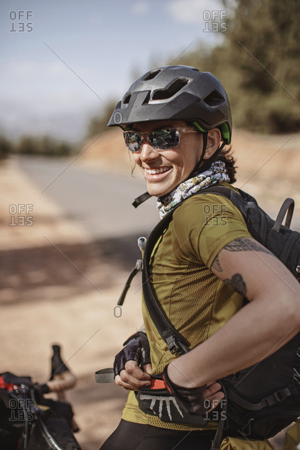 Morocco, Marrakesh-Safi - April 3, 2019: A female cyclist wearing sunglasses smiles while stopped on the road