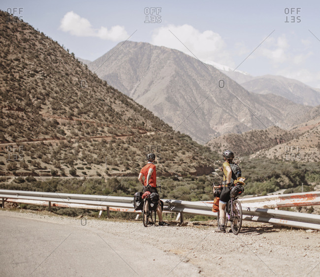 Morocco, Souss-Massa - April 3, 2019: A couple of cyclists look at the view of the atlas mountains, morocco