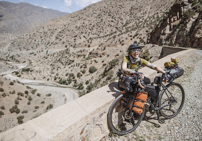 Morocco, Souss-Massa - April 3, 2019: Female cyclist smiles while bikepacking in the atlas mountains morocco