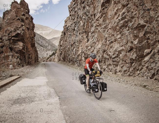Morocco, Souss-Massa - April 3, 2019: A cyclist rides through a rock cut on a mountain road in morocco