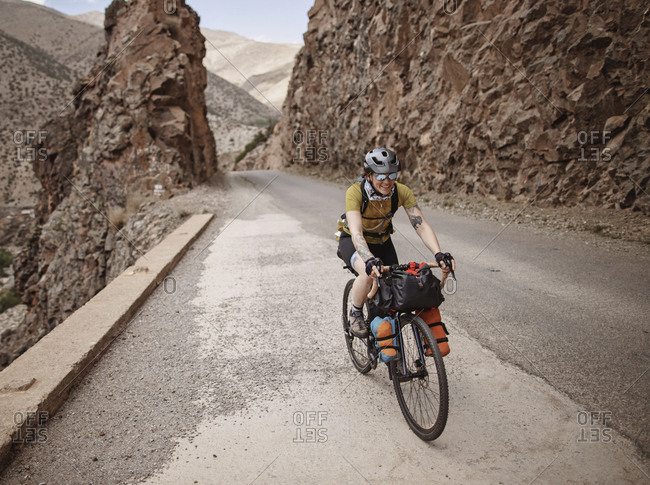 Atlas Mountains, Morocco - April 3, 2019: A female bike packer rides along a mountain road in the atlas mountain