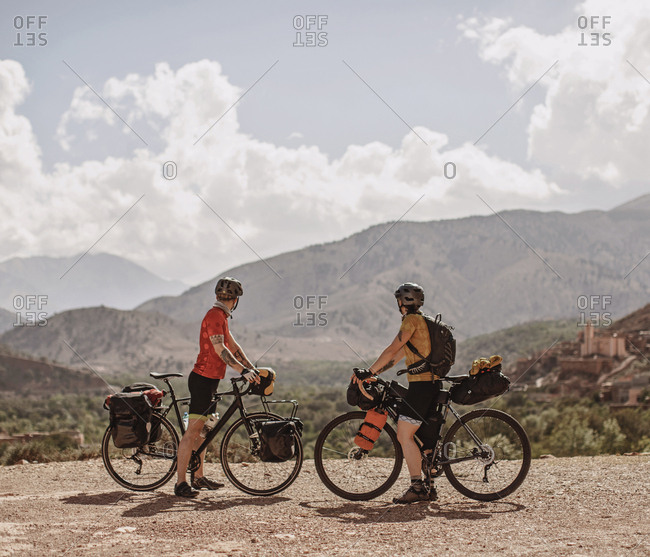 Atlas Mountains, Morocco - April 3, 2019: A couple of cyclists look at the view of the atlas mountains, morocco