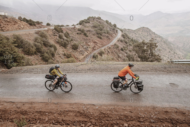 Morocco, Souss-Massa - April 4, 2019: A couple of cyclists biking on the hairpin tizi n test pass, morocco