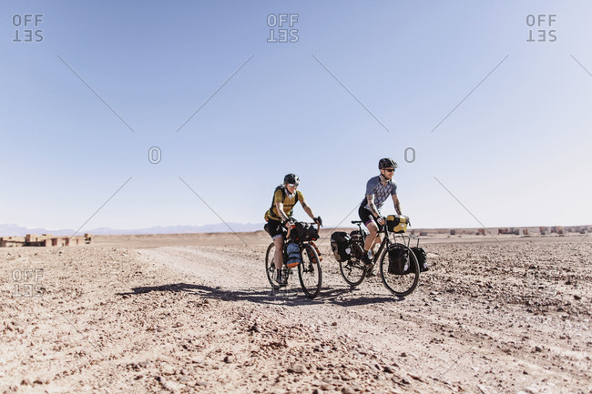 Sahara Desert, Morocco - April 8, 2019: Two smiling caucasian cyclists ride a desert dirt road in morocco