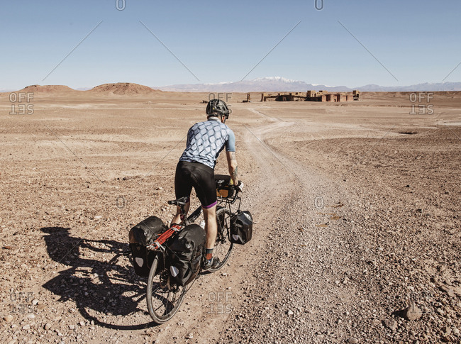 Morocco, Draa-Tafilalet, Ouarzazate - April 8, 2019: A cyclist rides through a desert toward ruins, ouarzazate, morocco