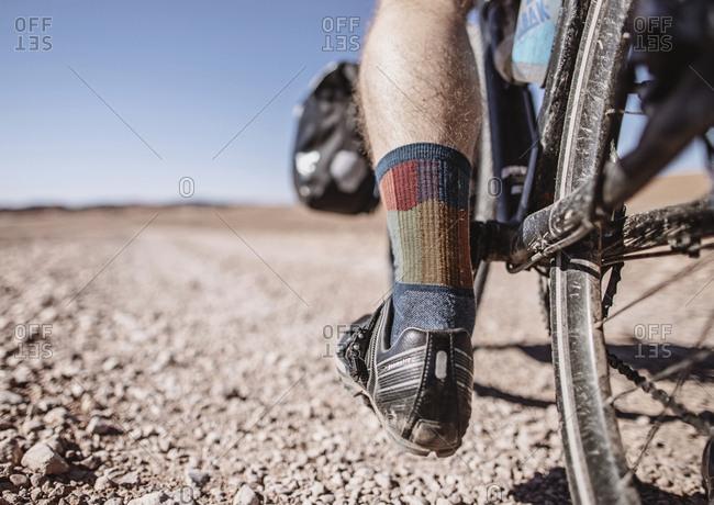 Sahara Desert, Morocco - April 8, 2019: A close up of a cyclist's socks and bike shoe, sahara desert, morocco