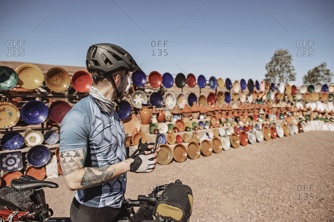 Morocco, Draa-Tafilalet, Ouarzazate - April 8, 2019: A male cyclist stops next to an outdoor ceramic market, morocco
