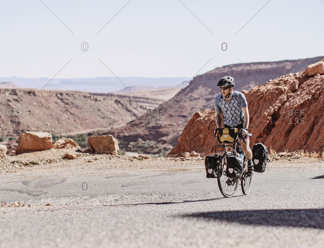 Atlas Mountains, Morocco - April 8, 2019: A man rides his bike up a steep road in the atlas mountains of morocco