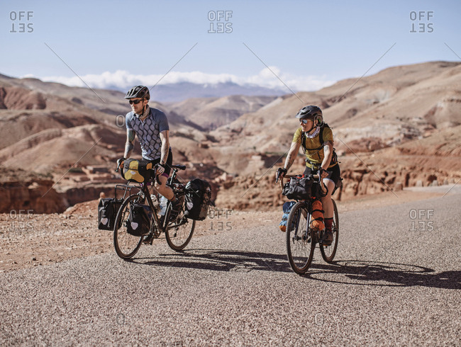 Atlas Mountains, Morocco - April 8, 2019: Two cyclists bike along remote mountain road in the desert of morocco