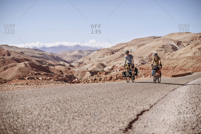 Morocco, Draa-Tafilalet, Telouet - April 8, 2019: Two bike packers ride along a road with desert mountains behind them