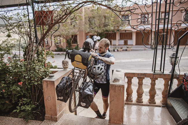 Atlas Mountains, Morocco - April 10, 2019: A male cyclist carries his bike on his shoulder up steps in morocco