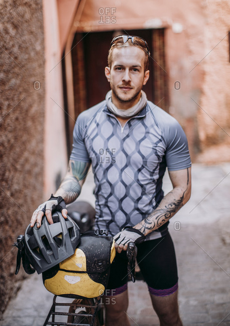 Morocco, Marrakesh-Safi, Marrakesh - April 10, 2019: A male cyclist stands for a portrait in a street in marrakesh, morocco