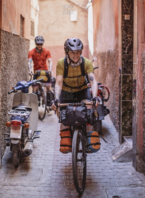 Morocco, Marrakesh-Safi, Marrakesh - April 11, 2019: Two cyclists ride their bikes through the narrow streets of marrakesh