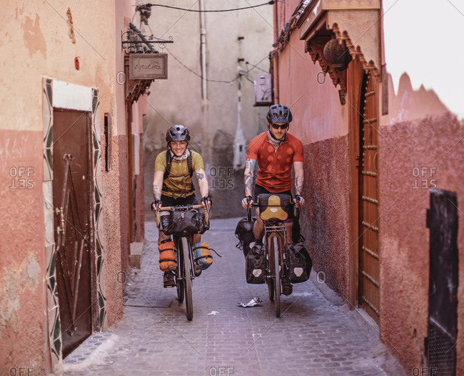Morocco, Marrakesh-Safi, Marrakesh - April 11, 2019: Two bikers ride through the narrow streets of the medina, marrakesh