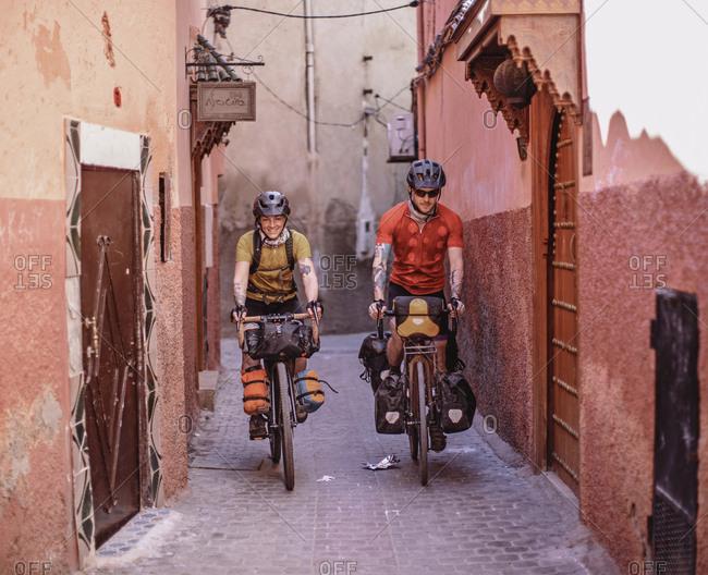 Morocco, Marrakesh-Safi, Marrakesh - April 11, 2019: Two bikers ride through the narrow streets of the medina, marrakesh