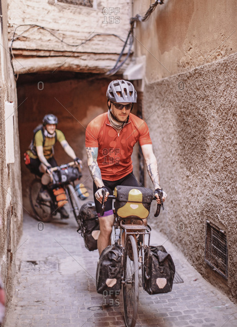Morocco, Marrakesh-Safi, Marrakesh - April 11, 2019: Two bike packers ride through the narrow streets of marrakesh, morocco