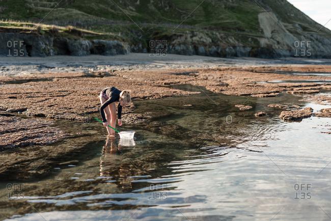 Girl exploring rock pools on the coast of New Zealand