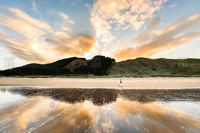 Beautiful sunset at Hawke's Bay, New Zealand with boy walking on beach