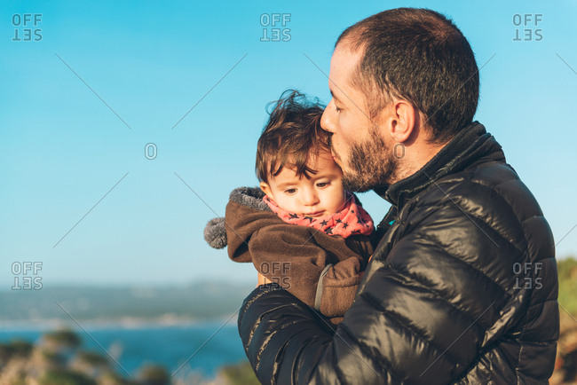 Father holding and kissing toddler girl near Monterey Bay, Big Sur, California, United States.