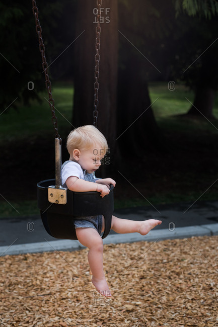 Baby boy sitting in swing at park