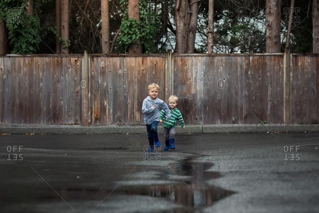 Two little boys running on wet street after rain